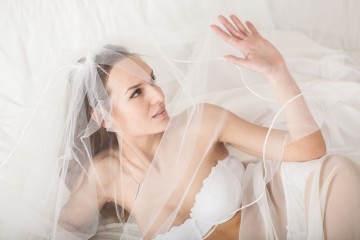 Young woman in bridal lingerie lying in bed and covering her face using veil